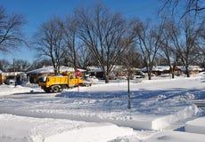 Gul lastbil för snöplog som gör klar insnöat bostadsområde royaltyfri foto