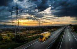 Gul lastbil på en huvudväg på solnedgången royaltyfri fotografi