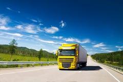 Gul lastbil på en väg Arkivfoto