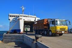 Gul lastbil som ut bär träplankor som är kommande från en stor färja på Natovi som landar närliggande Suva, Fiji Royaltyfria Foton