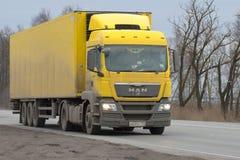 Gul lastbilMAN TGS av året för 2008 modell med halv-släpet på huvudvägen i den dystra marseftermiddagen Fotografering för Bildbyråer