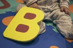 Gul leksak för bokstav B på en färgrik lekplats royaltyfri bild