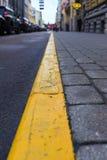 Gul linje mellan trottoaren och vägen i staden arkivfoto