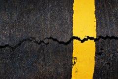 Gul linje på den spruckna asfaltvägen Arkivbild