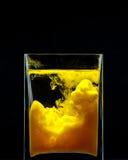 Gul målarfärg som virvlar runt i vatten på svart bakgrund Färgstänk av målarfärg i en glass krus Plan stil Royaltyfri Fotografi