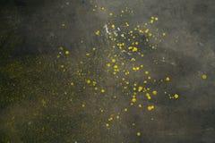 Gul målarfärg stänkte på ett cementgaragegolv arkivfoton