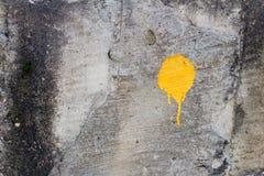 Gul målarfärgfläck på den gamla och smutsiga väggen Yttersidan av lura Royaltyfri Bild