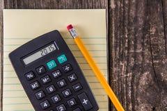 Gul minnestavlablyertspenna & räknemaskin på tappningskrivbordet royaltyfri bild