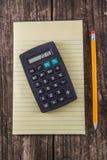 Gul minnestavlablyertspenna & räknemaskin på tappningskrivbordet arkivfoton