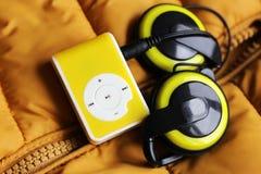 Gul musikspelare och härlig över huvudet hörlurar Fotografering för Bildbyråer