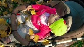 Gul nedgång för höstsidor på lite att behandla som ett barn flickan som sitter i en sittvagn Gulligt liten flickaleende i en virv lager videofilmer