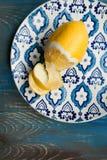 Gul ny citron på plattan med blåttmodellen Arkivbild