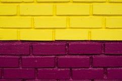 Gul och purpurfärgad tegelstenvägg Royaltyfri Foto