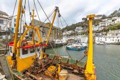 Gul och röd fiskebåt som förtöjas i den historiska Polperro hamnen, Cornwall arkivbild