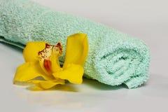 Gul orkidé med handduken på den vita bakgrunden - wellness & brunnsort Royaltyfria Foton