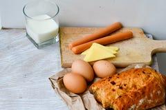 Gul ost, mjölkar, ägg bröd och korvar royaltyfri fotografi