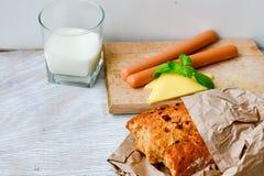 Gul ost, mjölkar, bröd och korvar royaltyfria foton