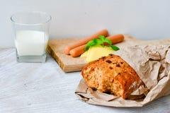 Gul ost, mjölkar, bröd och korvar royaltyfri foto