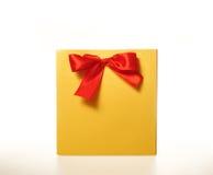 Gul pappers- gåvapåse med ett rött band på vit bakgrund Arkivfoto