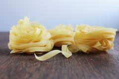 Gul pasta tre på trätabellen royaltyfria foton