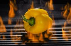 Gul peppar på ett varmt flammande galler Arkivfoto