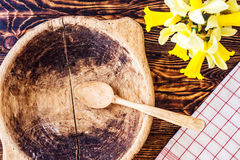 Gul pingstlilja med den träbunken, torkduken och skeden på brun träbakgrund, våren eller easter bakgrund, marsch Arkivfoto