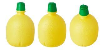 Gul plast- flaska med koncentrerad citronjuice arkivfoto