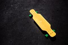 Gul plast- longboard på asfaltyttersidan royaltyfria foton