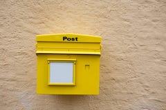 Gul postbox på väggen Arkivfoton