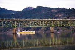 Gul pråm under bron över floden royaltyfria bilder