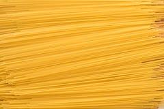 Gul rå torr spagetti, bakgrund, textur Arkivfoto