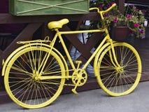 Gul retro cykel med en korg av blommor arkivfoto