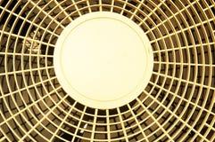 Gul rund aluminum metalltråd bak en stor fan med en fanimpeller inom Arkivbilder