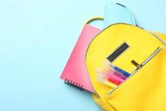 Gul ryggsäck med olika skolatillförsel arkivbild