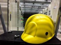 Gul säkerhetshjälm i elektriskt rum som lokaliseras under lyftt golv arkivfoton