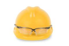 Gul säkerhetshjälm och skyddsglasögon som isoleras på vit bakgrund Arkivbild