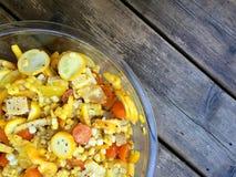 Gul sallad med havre, zucchini, tomater, peppar i den glass bunken Royaltyfri Fotografi