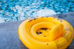 Gul simningcirkel på pölkanten royaltyfria foton