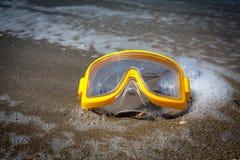 Gul simningmaskering på den sandiga stranden Royaltyfria Foton