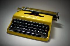 Gul skrivmaskin för tappning i stämningsmättad spotligh royaltyfri foto