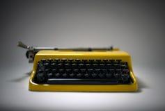 Gul skrivmaskin för tappning i stämningsmättad strålkastare royaltyfri bild
