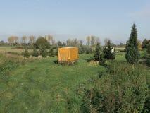 Gul släp på en grön lantgård royaltyfri bild