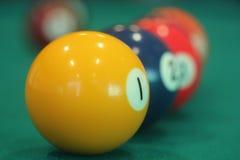 Gul snookerboll med nummer ett på det med andra färgrika bollar som i rad förläggas på en tabell Arkivfoton