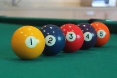 Gul snookerboll med nummer ett på det med andra färgrika bollar som i rad förläggas på en tabell Fotografering för Bildbyråer
