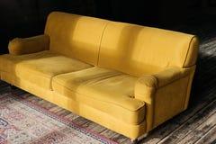 gul soffa på trägolv royaltyfri fotografi