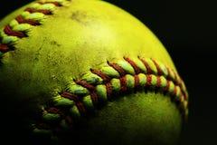 Gul softball på svart bakgrund Royaltyfria Bilder