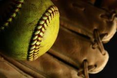 Gul softballcloseup med röda sömmar på en brun läderhandske arkivfoto
