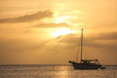 Gul solnedgång med segelbåten royaltyfria bilder