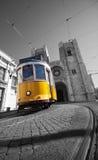 Gul spårvagn på bakgrunden av den Lissabon domkyrkan arkivfoton
