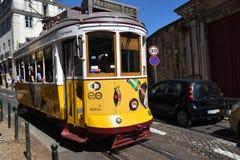 Gul spårvagn på en smal gata i Lissabon, Portugal Arkivfoto